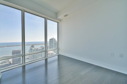 2nd Bedroom With A Large Closet & Gleaming Hardwood Flooring Facing Unobstructed Lake Views.