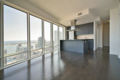 Bright Floor-To-Ceiling Wrap Around Windows With Gleaming Hardwood Flooring & A Smooth Ceiling Throughout Facing Stunning Unobstructed Lake Views.