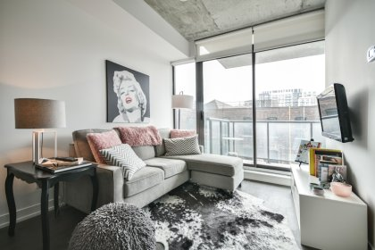 Bright Floor-To-Ceiling Windows With Customized Roller Shades & Hardwood Flooring Throughout.