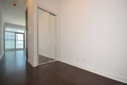 Suite Foyer With A Mirrored Closet & Hardwood Flooring.