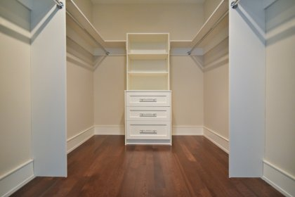 The Grand Master Bedroom With A Walk-In Closet and Hardwood Flooring.