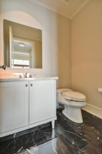 Powder Room With Marble Counter Top & Flooring.