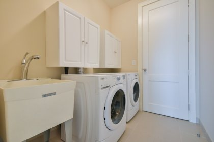 Separate Laundry Area With Laundry Sink and Built In Cabinets.