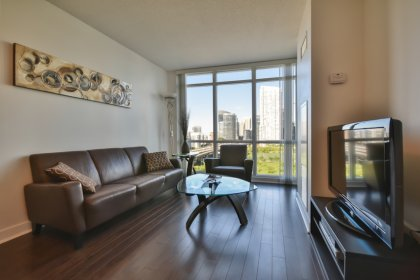Bright Floor-To-Ceiling Windows With Laminate Flooring Throughout Facing Unobstructed Park Views.