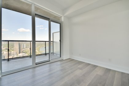 2nd Bedroom With Laminate Flooring,  A Mirrored Closet & A Walk-Out Balcony.
