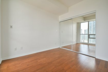 A Spacious Sized Master Bedroom With A Sliding Door, Large Mirrored Closet & Hardwood Flooring.
