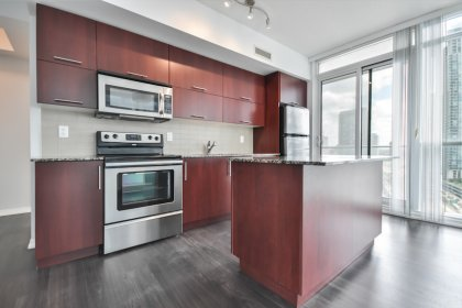 Designer Kitchen Cabinetry With Stainless Steel Appliances, Granite Counter Tops & A Centre Island Breakfast Bar.