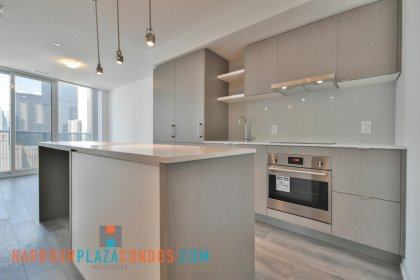 Designer Kitchen Cabinetry With Stainless Steel Appliances, Stone Counter Tops & A Breakfast Bar.