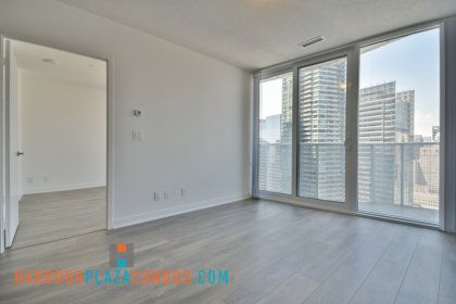 Living & Dining Areas With Bright Floor-To-Ceiling  Windows, Laminate Flooring Throughout & A  Private Balcony Facing Financial District Views.