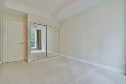 A Spacious Sized Master Bedroom With Mirrored Closets & Large Window.