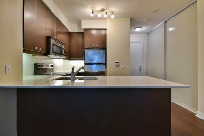 Designer Kitchen Cabinetry With Stainless Steel Appliances, Granite Counter Tops, Valance Lighting, An Undermount Sink & A Breakfast Bar.