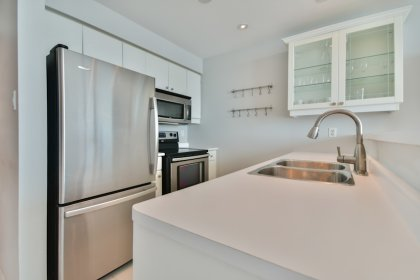 Designer Kitchen Cabinetry With Stainless Steel Appliances, Pot Lighting & A Breakfast Bar.