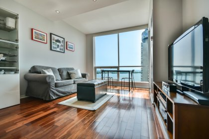 Bright Floor-To-Ceiling Windows With Gleaming Hardwood Flooring Throughout Facing Stunning Lake Views.