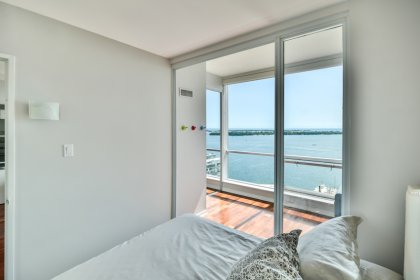 A Spacious Sized Master Bedroom With Gleaming Hardwood Flooring, A Mirrored Closet & In Bed Lake Views.