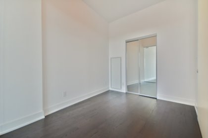 2nd Bedroom With Hardwood Flooring, Glass Sliding Doors & A Mirrored Closet.