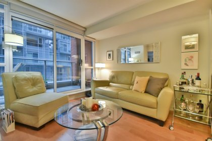 Bright Floor-To-Ceiling Windows With Newer Laminate Flooring & Roller Shades Throughout.
