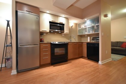 Designer Kitchen Cabinetry With Stainless Steel Appliances, Granite Counter Tops & A Glass Backsplash.
