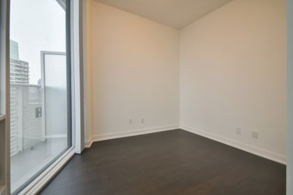 A Spacious Sized Master Bedroom With Laminate Flooring, A Large Window & Closet.