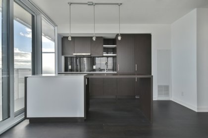 Designer Kitchen Cabinetry With Stainless Steel Appliances, Stone Counter Tops & A Centre Island.