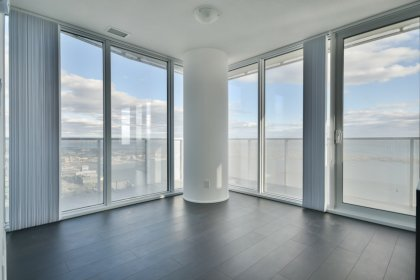 Bright Floor-To-Ceiling Wrap Around Windows With Laminate Flooring Throughout Facing Stunning Unobstructed Lake Views.