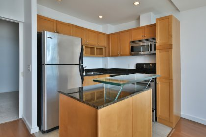 Designer Kitchen Cabinetry With Stainless Steel Appliances, Granite Counter Tops, Pot Lighting & A Glass Breakfast Bar.