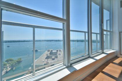 Bright Floor-To-Ceiling Windows With Hardwood Flooring Throughout The Living Areas Facing Stunning Unobstructed South Lake & Island Airport Views.