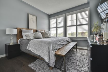 Spacious Sized Master Bedroom With A Custom Built-In Closet, California Window Shutters, Hardwood Flooring & A Large Window.