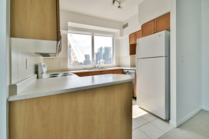 Designer Kitchen Cabinetry With A Stainless Steel Dishwasher & A Breakfast Bar.