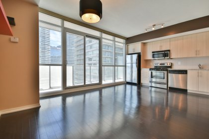 Bright Floor-To-Ceiling Windows With Hardwood Flooring Throughout The Living & Dining Areas.