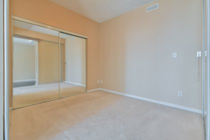 A Spacious Sized Master Bedroom With A Large Mirrored Closet & Glass Sliding Doors.