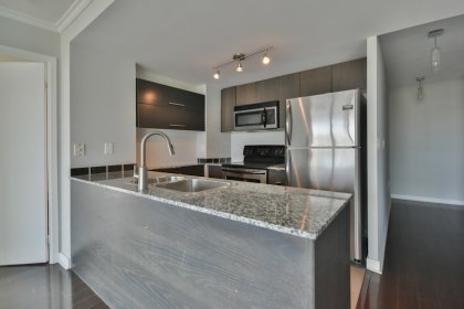 Designer Kitchen Cabinetry With Stainless Steel Appliances, Granite Counter Tops &  A Breakfast Bar Area.