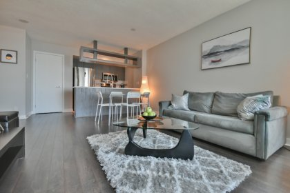 Open Concept Living Area With Laminate Flooring Facing Lake Views.