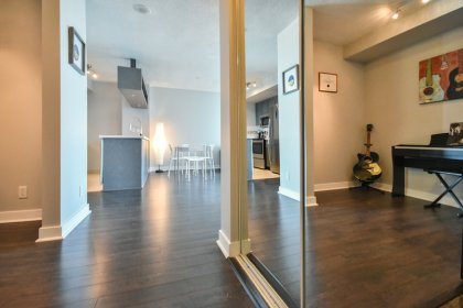Foyer Area With A Mirrored Closet & Laminate Flooring.