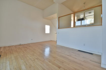 Open Concept Living Area With A Cathedral Ceiling And Hardwood Flooring With A Walk-Out To The Private Backyard Patio.