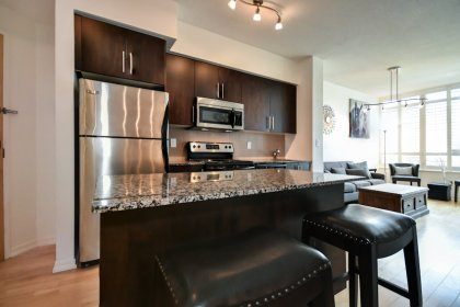 Designer Kitchen Cabinetry With Stainless Steel Appliances, Granite Counter Tops, An Undermount Sink & A Centre Island.
