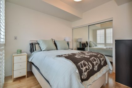 A Spacious Sized Master Bedroom With California Shutters, Hardwood Flooring & Mirrored Closets.
