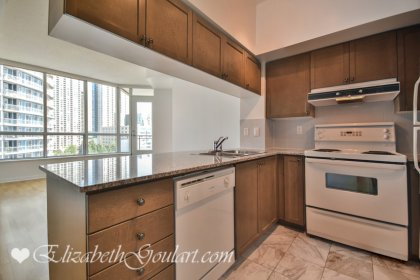 Designer Kitchen Cabinetry With Granite Counter Tops & A Breakfast Bar.