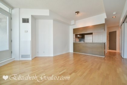 Open Concept Living & Dining Areas With Customized Roller Shades & Laminate Flooring.