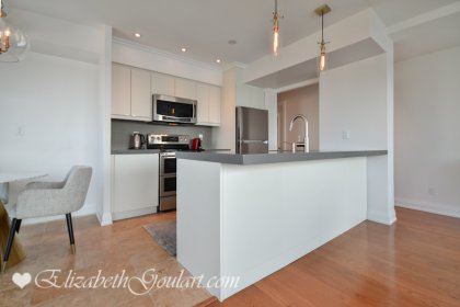 Designer Kitchen Cabinetry With Stainless Steel Appliances, Stone Counter Tops, An Undermount Sink, Breakfast Bar & An Eat-In Area.