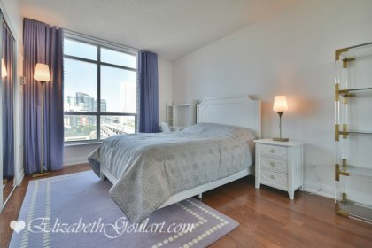 2nd Bedroom With Double Mirrored Closets, Gleaming Hardwood Flooring & A Large Window.