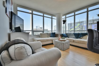 Bright Wrap Around Windows With Hardwood Flooring Throughout The Living Areas Facing C.N. Tower Views.