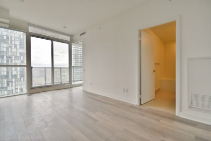 Bright Floor-To-Ceiling Windows With Laminate Flooring Throughout.
