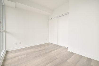 A Spacious Sized Master Bedroom With A Sliding Door & A Large Window.