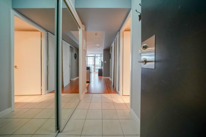 A Large Foyer With Mirrored Closet And Custom Built In Shoe Shelving.