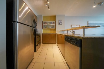 Designer Kitchen Cabinetry With Stainless Steel Appliances, Granite Counter Tops & A Breakfast Bar.