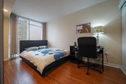 A Spacious Sized Master Bedroom With Bright Floor-To-Ceiling Windows Including Laminate Flooring Throughout & A Pot Lighting Dimmer Switch.