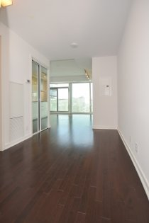 Suite Foyer With Mirrored Closet & Hardwood Flooring.