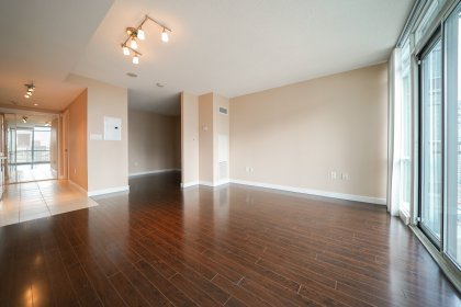 Bright Floor-To-Ceiling Windows With Laminate Flooring Throughout & Balcony CN Tower Views.