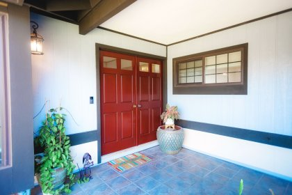 Double solid wood doors. Large covered entryway.