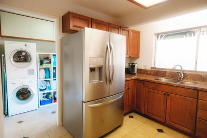 Indoor laundry room and newer stainless steel refrigerator.